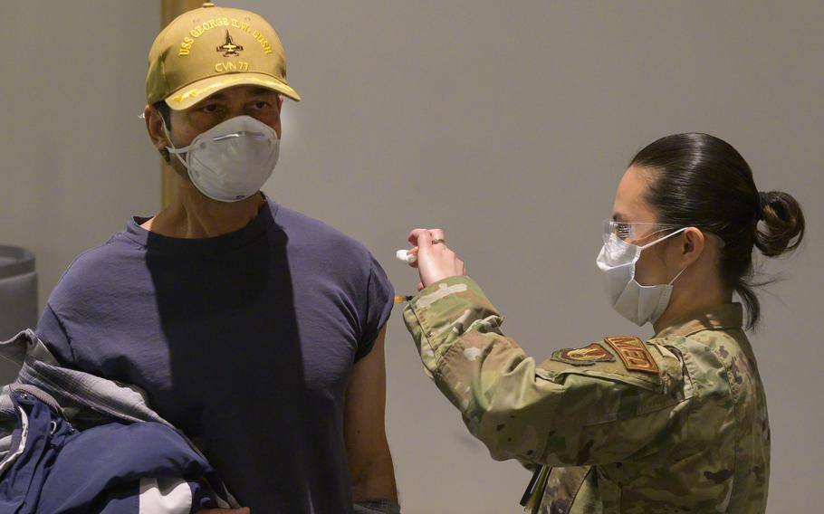 Tech. Sgt. Hazel Mangabat, 88th Healthcare Operations Squadron, injects Dr. Octavio Borges, a contractor with the U.S. Air Force School of Aerospace Medicine, with the COVID-19 vaccine Jan. 8, 2021, on Wright-Patterson Air Force Base, Ohio.