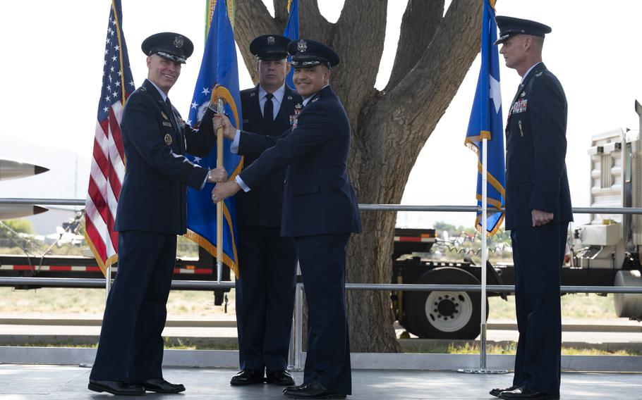 U.S. Air Force Maj. Gen. Michael J. Lutton, left, 20th Air Force commander, passes the guidon to incoming commander Col. Jason F. Vattioni, right, at Kirtland Air Force Base, New Mexico, June 22, 2021.  Vattioni assumed command of the 377th Air Base Wing as the installation commander.