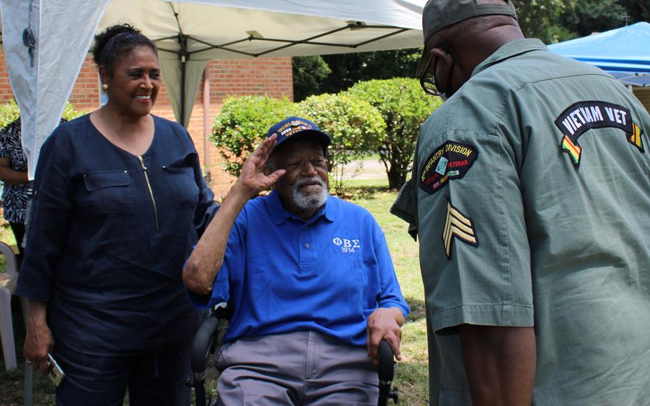 Retired Lt. Col. Louis Frazier Martin and Sgt. Albert W. Cooks salute during Martin's 104 birthday celebration in Chesterfield, Va. on July, 3, 2021. Also pictured is Martin's daughter Sheila Martin Brown.