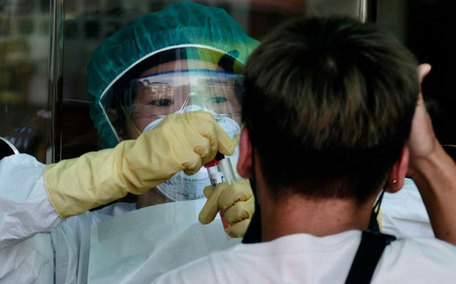 A medical staffer collects a sample from a local resident during a COVID-19 corona virus testing at the Xindian District in New Taipei City on May 21, 2021.