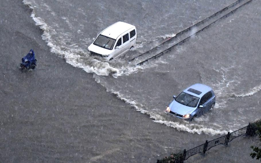 In this photo released by Xinhua News Agency, vehicles pass through floodwaters in Zhengzhou in central China's Henan Province on Tuesday, July 20, 2021. At least a dozen people died in severe flooding Tuesday in a Chinese provincial capital that trapped people in subways and schools, washed away vehicles and stranded people in their workplaces overnight.