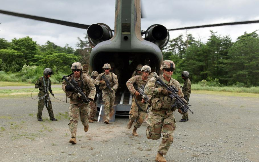 U.S. soldiers sprint off a Japan Ground Self-Defense Force helicopter during air-assault training at Aibano Training Area, Japan, during Orient Shield drills, July 1, 2021.