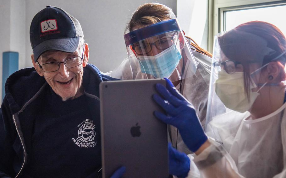 U.S. Army veteran Skip, left, uses an iPad to speak to his family with the help of nurse manager Laurie Nicol, center, and recreation therapist Kristen Weber at Holyoke Soldiers Home in Holyoke, Mass., where he was in isolation due to COVID-19, April 20, 2020. Using technology to connect with others during coronavirus lockdowns and quarantines is thought to be one reason why suicidal thoughts among veterans fell during the pandemic, says a study published Aug. 25, 2021.
