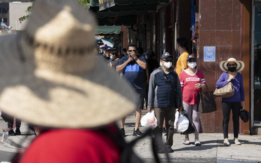 Visitors to Los Angeles' Chinatown wear masks even outdoors after L.A. County began requiring them to be worn in public indoors.