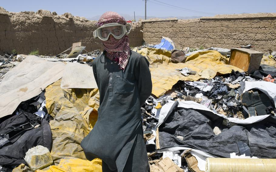Mohammed Daoud, 14, wears U.S. military goggles as he scavenges trash left behind by U.S. and NATO troops as they pack up from Bagram Airfield, Afghanistan. Workers at trash yards pick through garbage that leaves the base on trucks, but said troops have been careful to destroy most things.