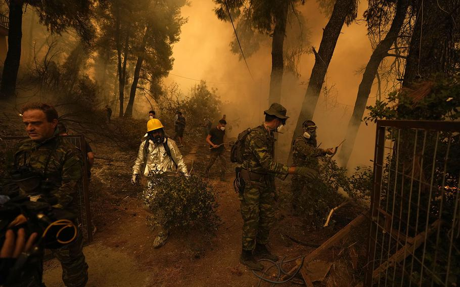 People try to extinguish the flames during a wildfire at Pefki village on Evia island, about 118 miles north of Athens, Greece, Sunday, Aug. 8, 2021.