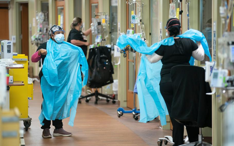Nurses prepare to enter a COVID-19 patient's room inside an ICU unit at the Jennie Sealy Hospital on the Galveston campus of the University of Texas Medical Branch.
