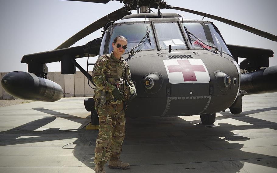 Staff Sgt. Brianna Pritchard, an Army National Guard UH-60 Black Hawk helicopter mechanic from Anchorage, Alaska, poses in front of a Task Force Phoenix UH-60 Black Hawk medical evacuation helicopter at al Asad Air Base, Iraq.