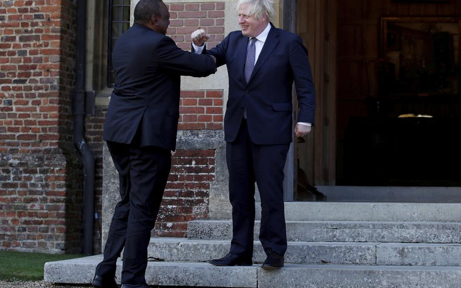 Britain's Prime Minister Boris Johnson greets Kenya's President Uhuru Kenyatta, left, at Chequers, the official country residence of the British Prime Minister July 28 near Aylesbury, England.