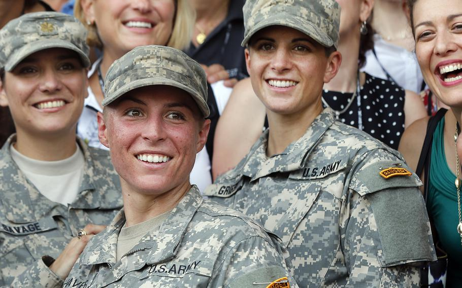 Army 1st Lt. Shaye Haver, center, and Capt. Kristen Griest, right, pose for photos with other female West Point alumni after an Army Ranger school graduation ceremony at Fort Benning, Ga., on Aug. 21, 2015.