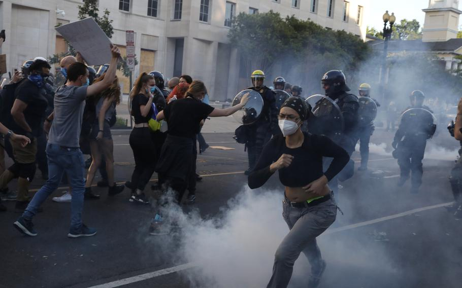 Demonstrators move away from police near Lafayette Square on June 1, 2020.