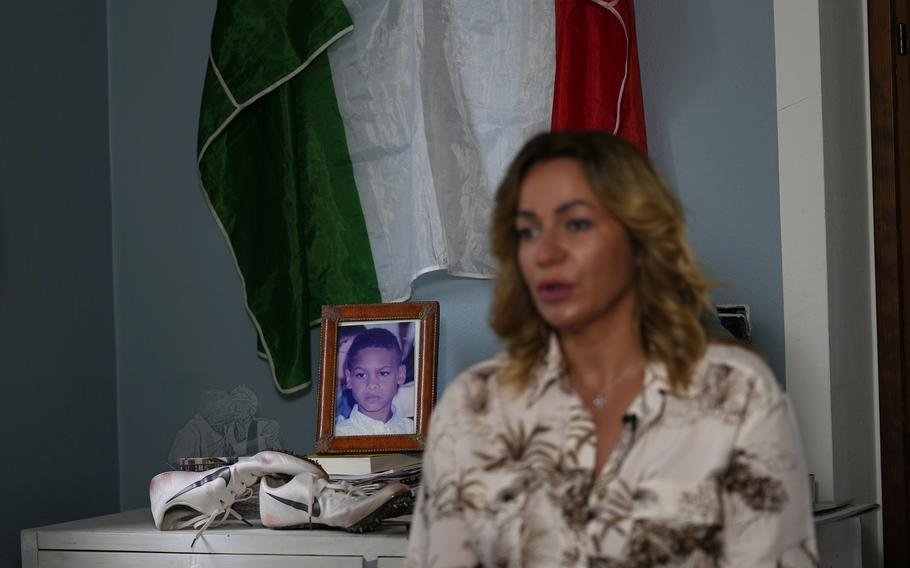 Viviana Masini, mother of Italy's Lamont Marcell Jacobs, shows a corner in her home, devoted to the winner of the 100 meters at the Tokyo Olympics, with an old pair of running shoes, a photo of him as a child and the Italian flag, in Manerba del Garda, Italy, Monday, Aug. 2, 2021.