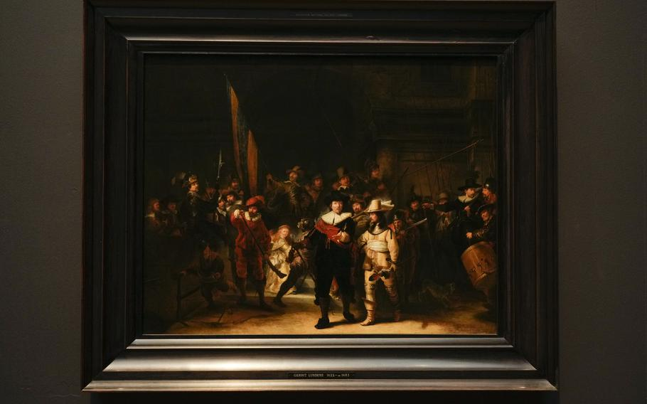 A copy of the Night Watch attributed to painter Gerrit Lundens served as the basis for artificial intelligence allowing Rembrandt's biggest painting the Night Watch to get bigger, is displayed next to the painting in Amsterdam, Netherlands, Wednesday, June 23, 2021. The Dutch national museum and art gallery reveals findings from a long-term project to examine in minute detail Rembrandt van Rijn's masterpiece the Night Watch.