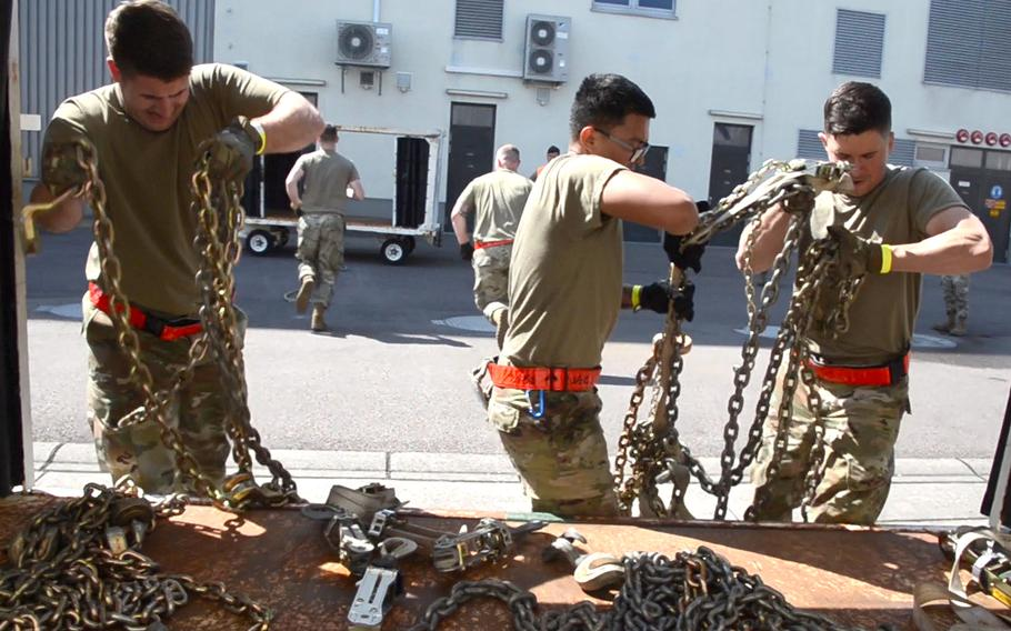 Capt. Trevor Chasteen, left, Senior Airman Gerald Dinio, center, and Airman 1st Class Mitchell Lagrange load chains onto a cart after carrying them around 30 feet during the endurance event of the 721st Aerial Port Squadron Multi-Capable Airmen Rodeo at Ramstein Air Base, Germany, July 23, 2021.