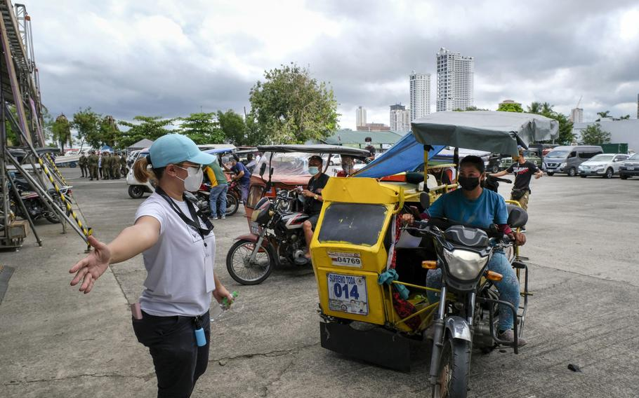 A health worker directs motorcycle taxi drivers at a COVID-19 drive-thru vaccination site set up at the Philippine International Convention Center in Manila, Philippines, on June 22, 2021.