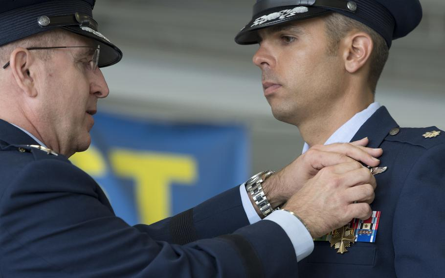 U.S. Air Force Lt. Col. Christopher McCall, 73rd Expeditionary Special Operations Squadron Shadow 71 aircraft commander, receives the Distinguished Flying Cross from Lt. Gen. Jim Slife, commander of Air Force Special Operations Command, during a ceremony at Hurlburt Field, Fla., June 22, 2021.