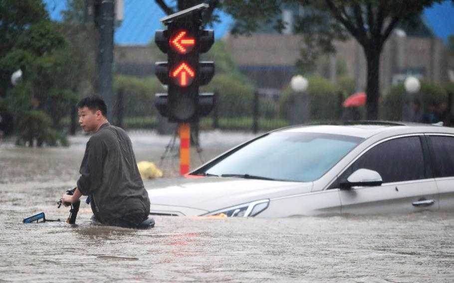 A man rides a bicycle through a flooded intersection in Zhengzhou in central China's Henan Province Tuesday.