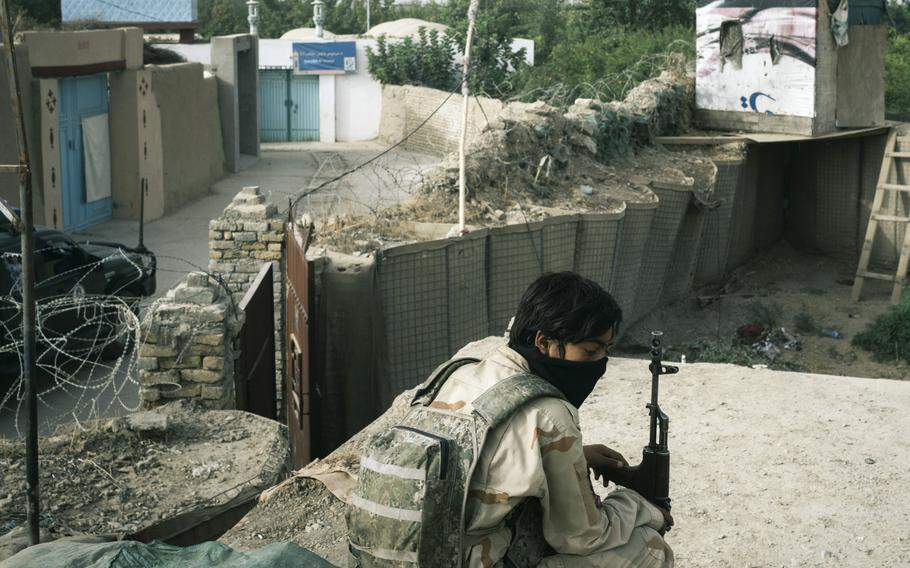 A policeman sits in an outpost in Kandahar, Afghanistan, as Afghan security forces find themselves engaged in a battle with the Taliban inside the city limits.