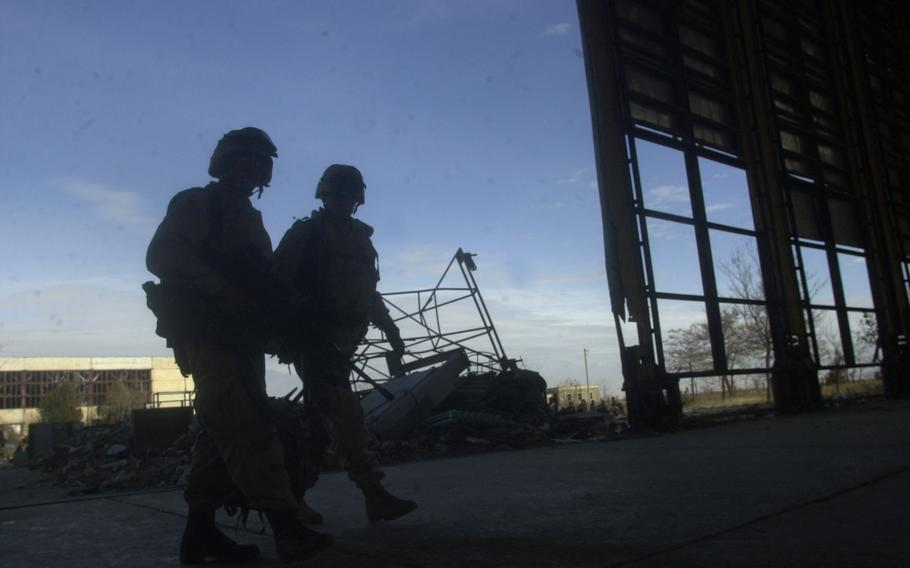 A pair of 10th Mountain Division soldiers patrol through a recently cleared out hangar on Bagram Airfield in Afghanistan, in December 2001. The U.S. has fully withdrawn from the airfield, once the largest American base in the country, a U.S. defense official confirmed Friday.