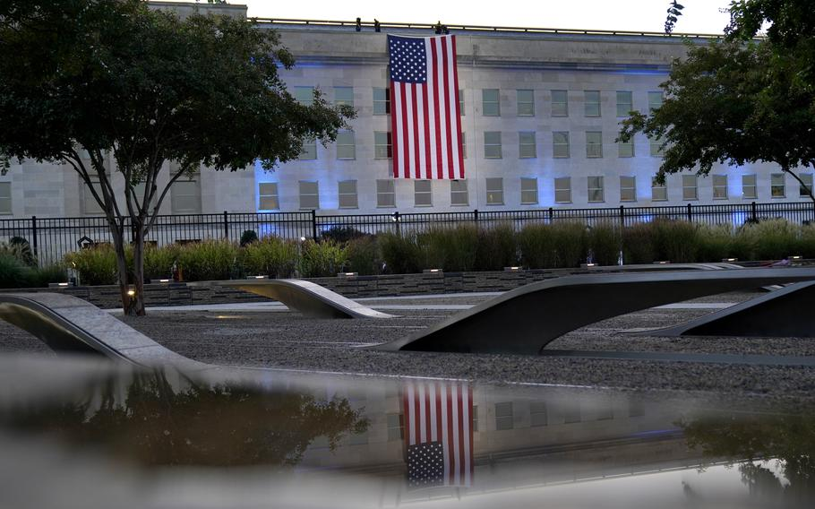 An American flag is unfurled at the Pentagon in Washington, Saturday, Sept. 11, 2021, at sunrise on the morning of the 20th anniversary of the terrorist attacks. The American flag is draped over the site of impact at the Pentagon. In the foreground, the National 9/11 Pentagon Memorial, opened in 2008 adjacent to the site, commemorates the lives lost at the Pentagon and onboard American Airlines Flight 77.