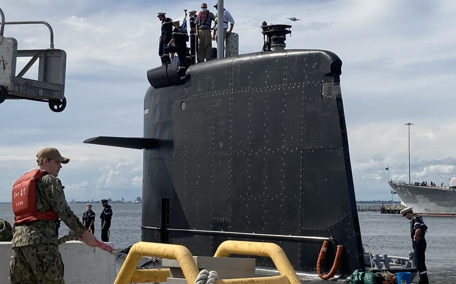 A U.S. Navy sailor helps the French submarine Améthyste moor at Naval Station Norfolk on Sept. 16 2021.