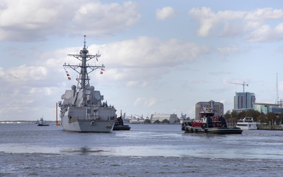 Tugboats maneuver USS Gravely out to sea as the ship gets underway for sea trials in 2020.