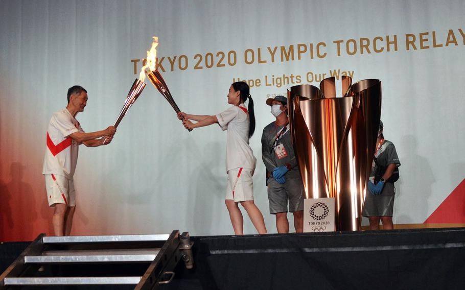 Torch relay runners from Hamura, a city near Yokota Air Base, pass the Olympic flame during an indoor ceremony in Tachikawa, Japan, Monday, July 12, 2021.