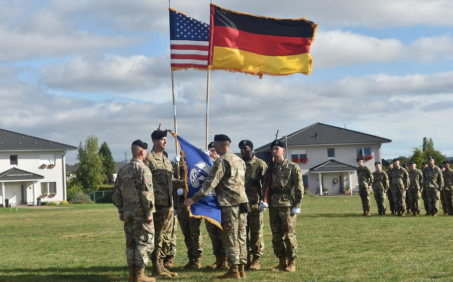 Command Sgt. Maj. Michael Carlan unfurls the flag of a new task force, which was activated at a ceremony on Clay Kaserne in Wiesbaden, Germany, on Sept. 16, 2021.