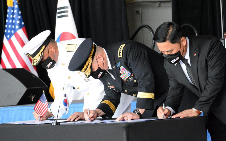 Rear Adm. Darius Banaji, left, deputy director of operations for DPAA; Gen. Paul LaCamera, commander of U.S. Forces Korea and United Nations Command, center; and Heo Wook Goo, director of South Korea's KIA Recovery and Identification agency sign documents officially transferring service members' remains at Joint Base Pearl Harbor-Hickam, Hawaii, Wednesday, Sept. 22, 2021.