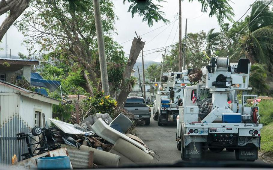 Two utility maintenance trucks navigate a narrow street cluttered with debris near San Juan, Puerto Rico, on Nov. 10, 2017, as National Guard members try to restore electrical power months after Hurricane Maria devastated the island.