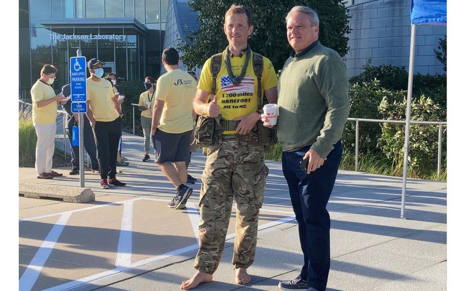 Chris Brannigan, who is walking 1,200 miles barefoot from Maine to North Carolina to raise research funding for his daughter's rare disease, stands with Farmington Town Council member Brian Connolly outside The Jackson Lab at the UConn Health campus on Sunday Sept. 19, 2021.