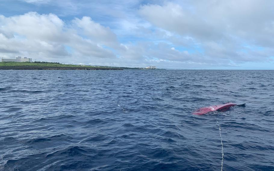 A kayak attached to a rope is flipped over half a mile off the coast of Cape Zanpa, Okinawa, June 13, 2021. It had been used by four Japanese men who found themselves stranded off the coast before being rescued by an airman and a civilian from Kadena Air Base.