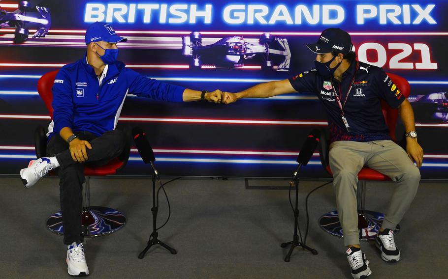 Haas driver Mick Schumacher of Germany, left, and Red Bull driver Sergio Perez of Mexico greet each other with a fist bump as they attend a media conference at the Silverstone circuit July 15 Silverstone, England.