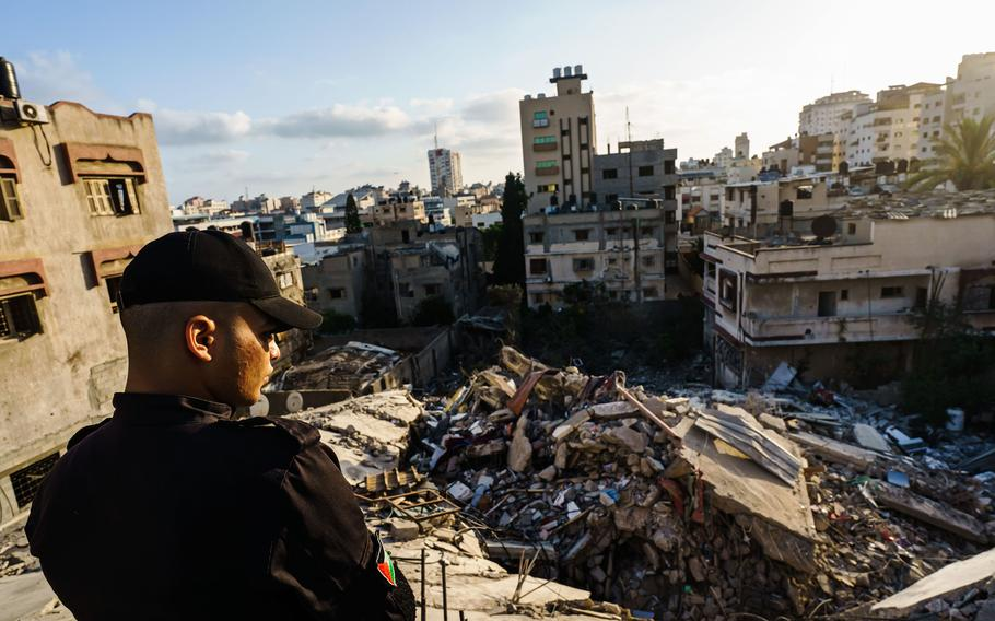 Police officers inspect the ruins of Samir Mansour's bookstore and nearby buildings, which were destroyed by Israeli bombardment during the last escalation between Israel and Gaza military factions, in Gaza City on Saturday, May 29, 2021.