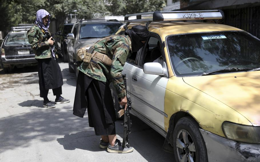 Taliban fighters search a vehicle at a checkpoint on the road in the Wazir Akbar Khan neighborhood in the city of Kabul, Afghanistan on Aug. 22, 2021.