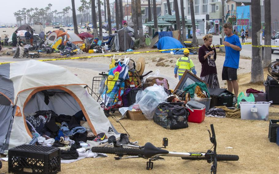 A couple experiencing homelessness waits for outreach workers at an encampment in the Venice Beach area of Los Angeles on July 2, 2021.