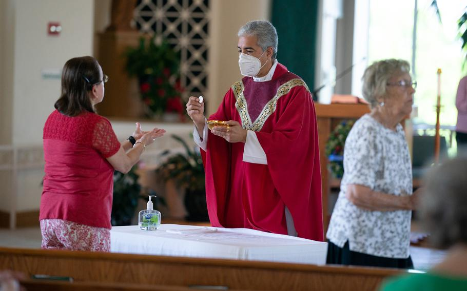 Monsignor Edward Filardi of St. Paul Catholic Church in Damascus, Md., leads a Saturday service. He sanitized his hands and put a mask on before giving Holy Communion in front of tables with sanitizer.