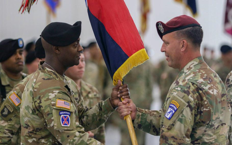 Lt. Gen. Michael E. Kurilla, XVIII Airborne Corps commander (right), passes the 10th Mountain Division colors to Brig. Gen. Milford Beagle Jr., during the division change of command ceremony July 12 at Wheeler-Sack Army Airfield.