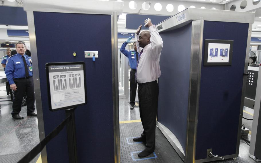 A volunteer passes through the first full body scanner installed at O'Hare International Airport in Chicago on March 15, 2010. The technology produces a cartoon-like outline rather than naked images of passengers by using X-rays.