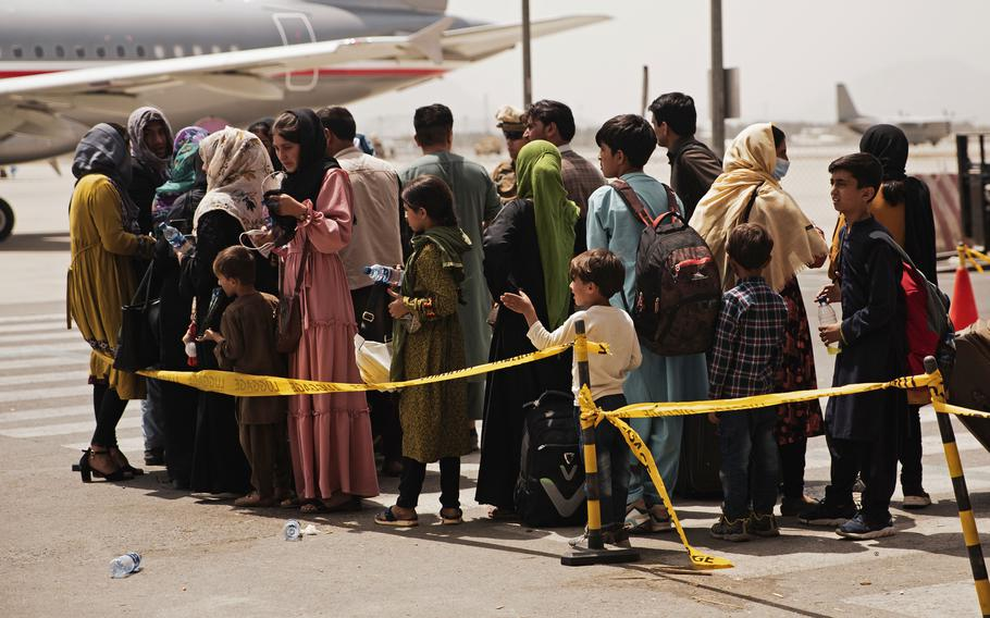 Civilians prepare to board a plane during an evacuation at Hamid Karzai International Airport, Kabul, Afghanistan, Aug. 18, 2021. U.S. Marines are assisting with the evacuation of people from Afghanistan following the Taliban's takeover.