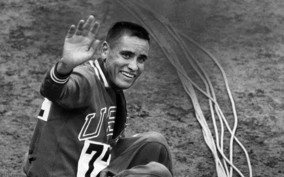 Billy Mills, a U.S. Marine, waves after winning Olympic gold in the 10,000-meter event at the Tokyo Olympics in 1964. Mills won a dramatic, elbow-jabbing, traffic-jam stretch run, beating out Mohammed Gamoudi of Tunesia, who got silver, and world record holder and favorite Ron Clarke of Australia, who captured the bronze.
