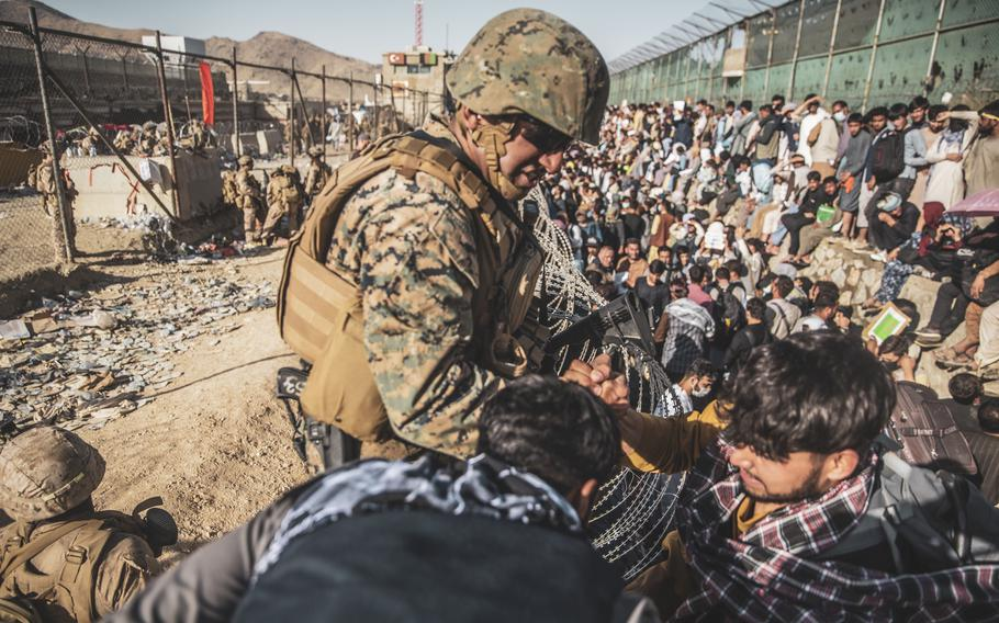 A U.S. Marine assists an Afghan at Hamid Karzai International Airport in Kabul on Aug. 26. The airlift evacuation, which took just over two weeks, saved more than 124,000 people.
