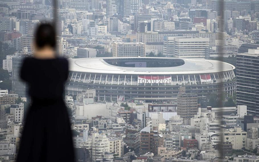 A woman takes photos of the Tokyo skyline, including the Olympic Stadium, from a Shibuya observatory, Tuesday, July 13, 2021.