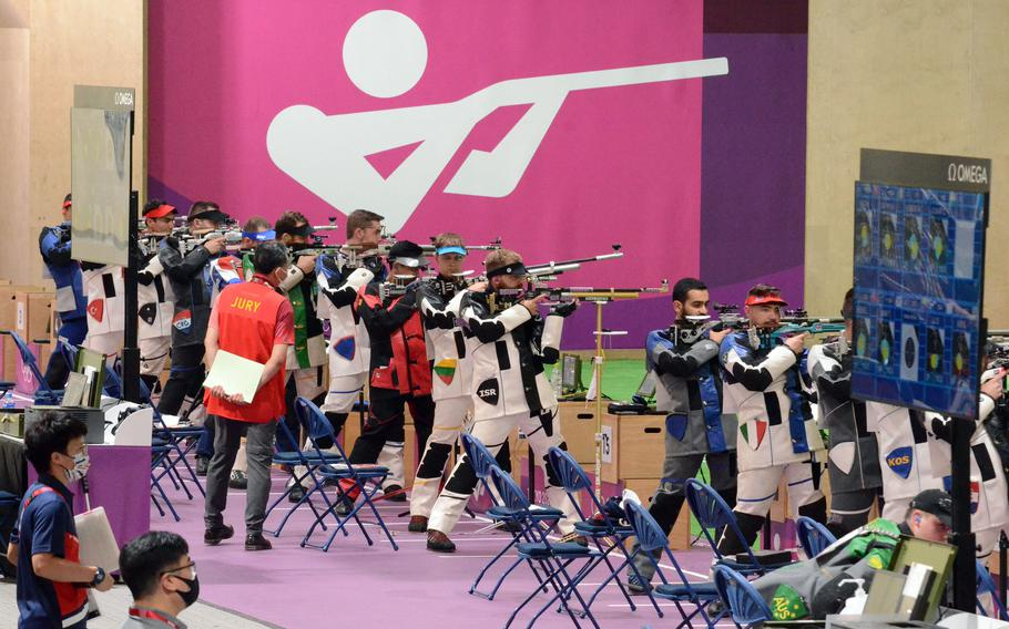 Athletes fire rifles at targets 10 meters away during an Olympic qualifying round at Camp Asaka, Japan, Saturday, July 24, 2021.