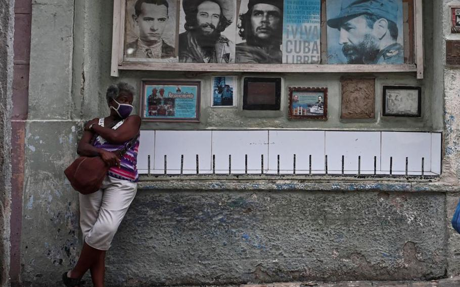 An elderly woman stands next to pictures of Cuban late leaders in a street of Havana, on July 14, 2021.
