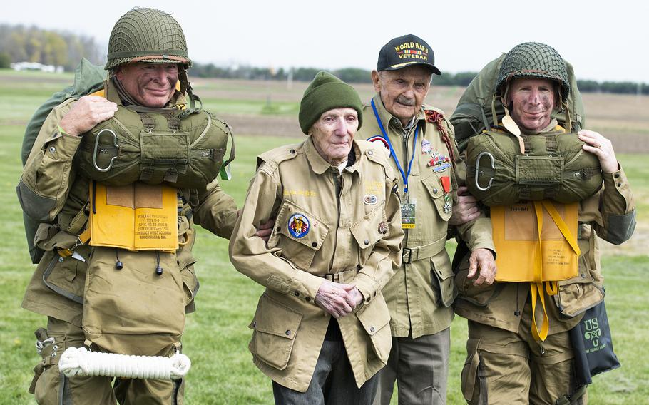 """WWII airborne demonstration team members walk with WWII veterans Jim """"Pee Wee"""" Martin, center left, and Dan McBride as they exit the drop zone during a 100th birthday celebration held in Martin's honor, April 23, 2021, in Xenia, Ohio. Both McBride and Martin, served as paratroopers assigned to 101st Airborne Division out of Fort Campbell, Kentucky."""