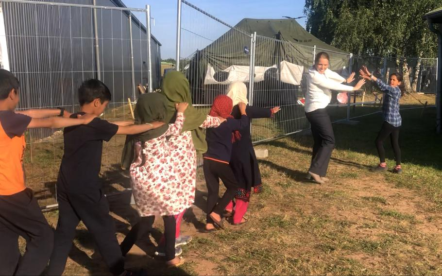 Volunteer teacher Morgan Guinn, second from right, and one of her Afghan students, Heri, right, lead other evacuee children to an Army tent on Rhine Ordnance Barracks for English lessons, Sept. 23, 2021.