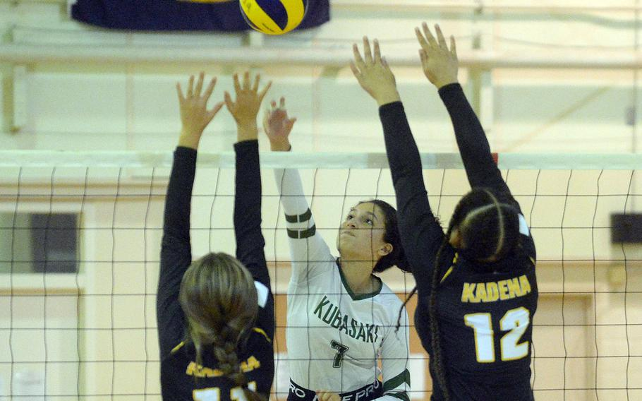 Kubasaki's Sophia Grubbs spikes thorugh the double block of Kadena's Presley Pearce and Malana Williams during Thursday's Okinawa volleyball match.