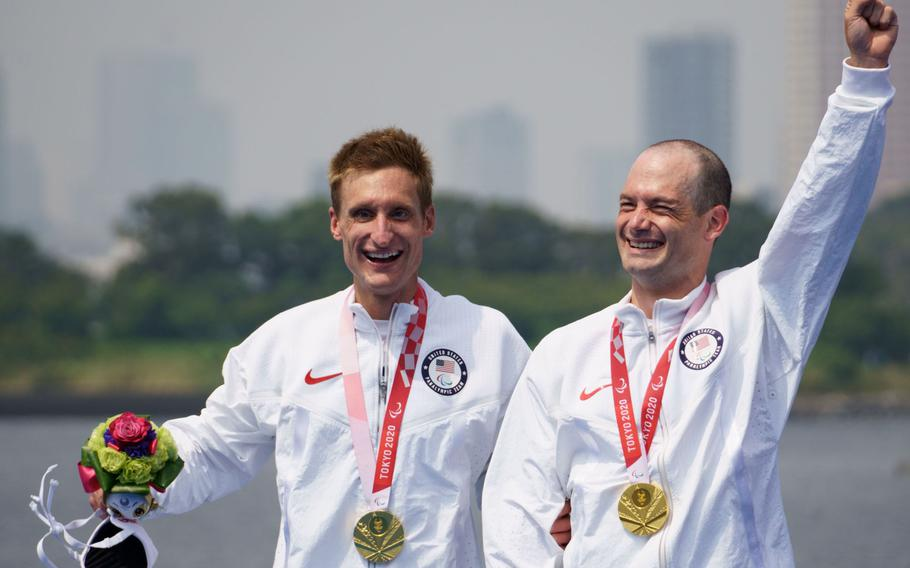 Navy veteran Bradley Snyder, left, who lost his sight during an Afghanistan blast in 2011, and Greg Billington ceberate after winning a gold medal in the Paralympic triathlon at Odaiba Marine Park, Tokyo, Saturday, Aug. 28, 2021.