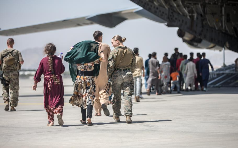 A Marine with the 24th Marine Expeditionary Unit walks with the children during an evacuation at Hamid Karzai International Airport, in Kabul, Afghanistan, on Tuesday, Aug. 24, 2021.